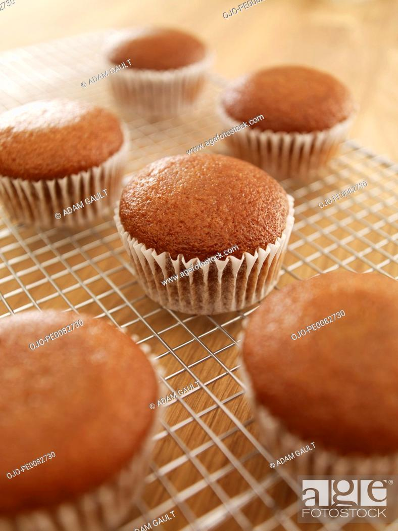 Stock Photo: Close up of cupcakes cooling on wire rack.