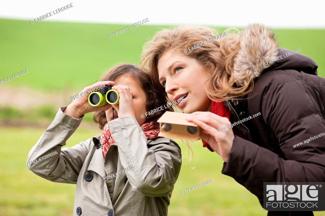 Stock Photo: Boy looking through binoculars standing with his mother.