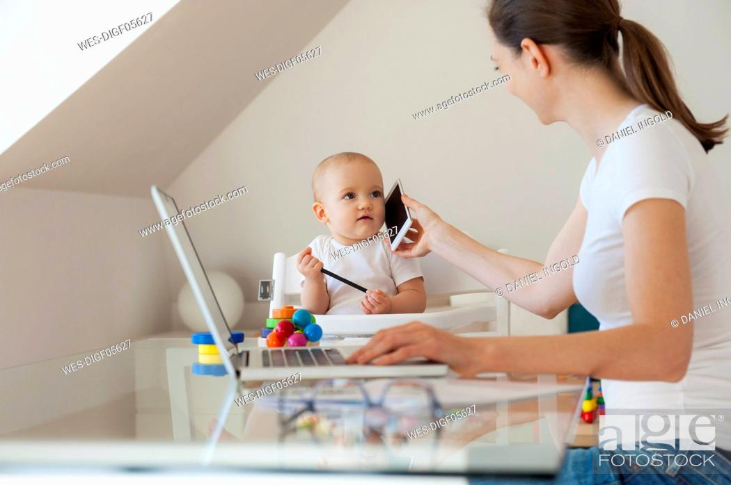 Stock Photo: Mother working with little daughter playing at table at home.