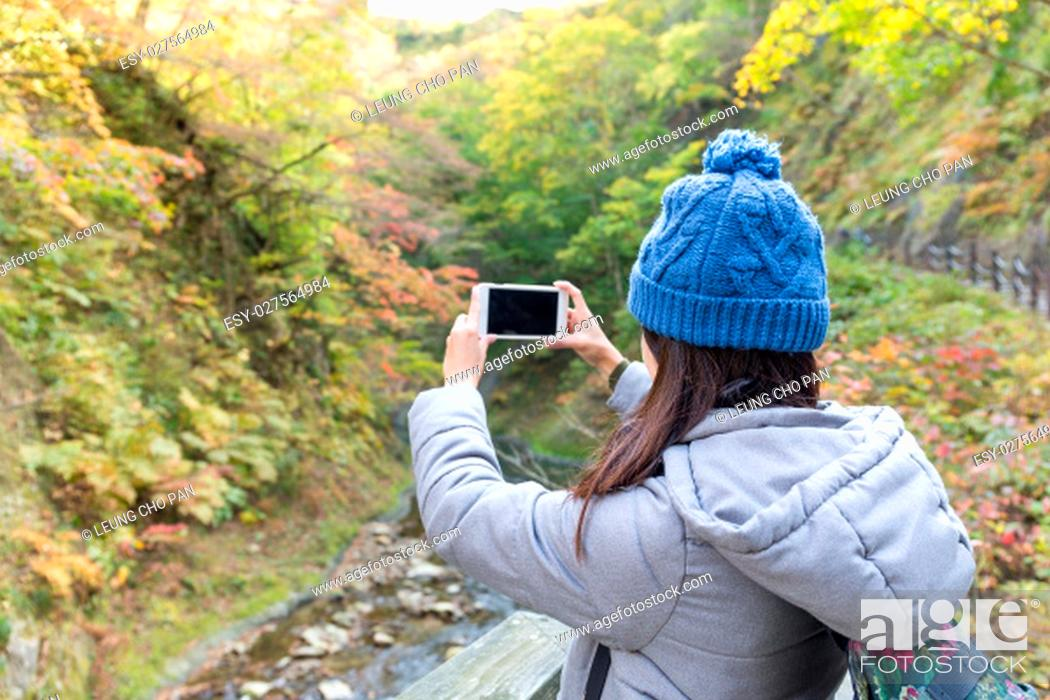 Stock Photo: Woman taking photo in forest.