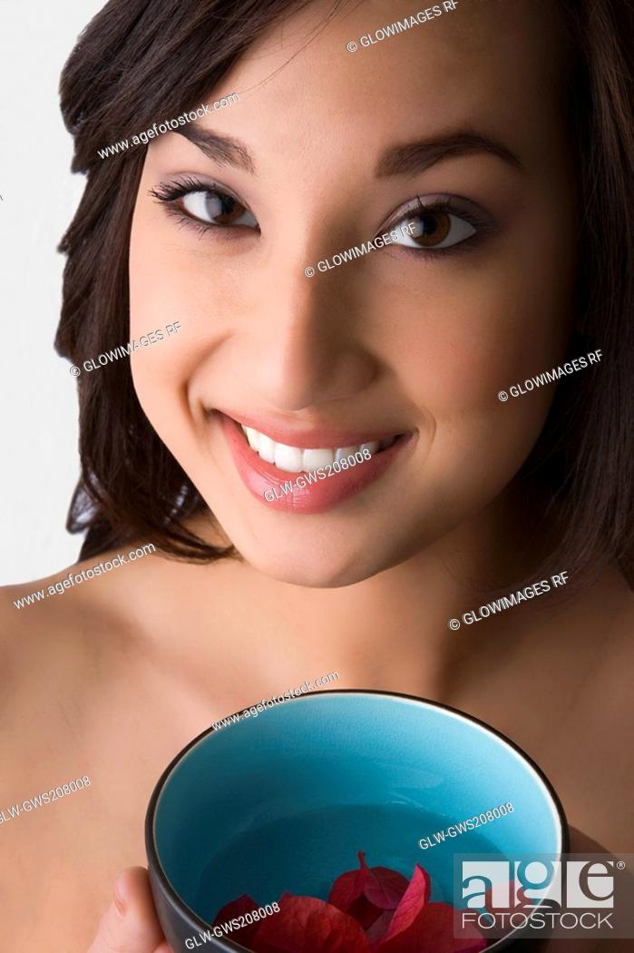Stock Photo: Portrait of a young woman holding a bowl of water with floating leaves.