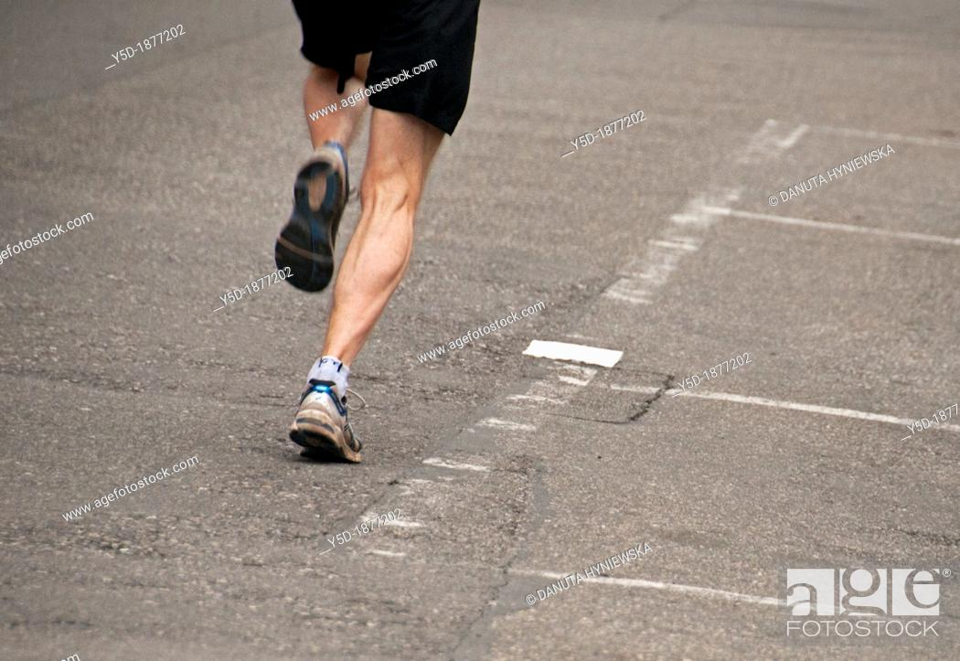 Stock Photo: one man jogging on the street, legs only, Geneva, Switzerland.