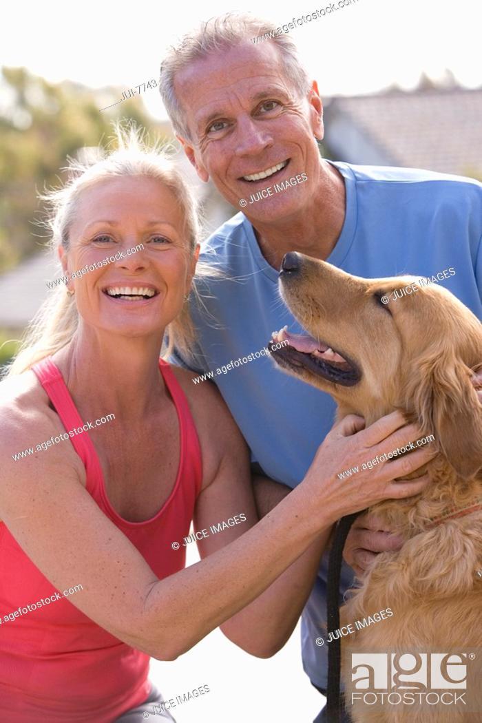 Stock Photo: Active senior couple, in sportswear, stroking golden retriever, smiling, portrait.