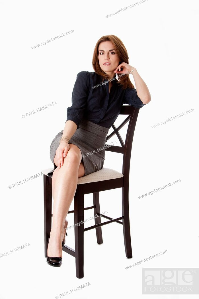 Stock Photo: Beautiful brunette business woman sitting wearing gray skirt and blue blouse with hand on leg with legs crossed, isolated.