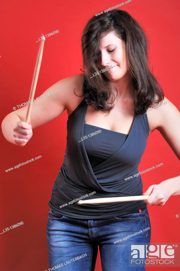 Stock Photo: A young woman playing with drumsticks.