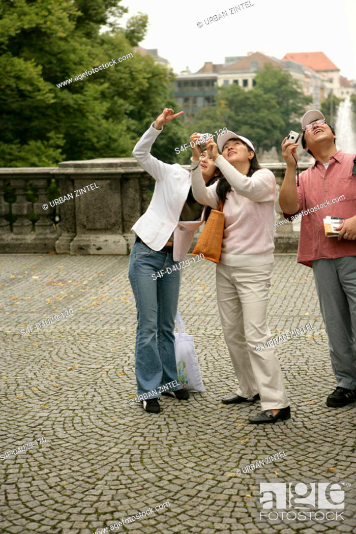 Stock Photo: Three Asian people with cameras looking up, focus on foreground.