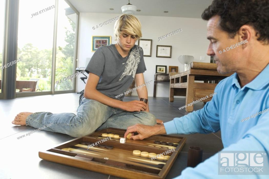 Stock Photo: Father and son playing backgammon, indoors.