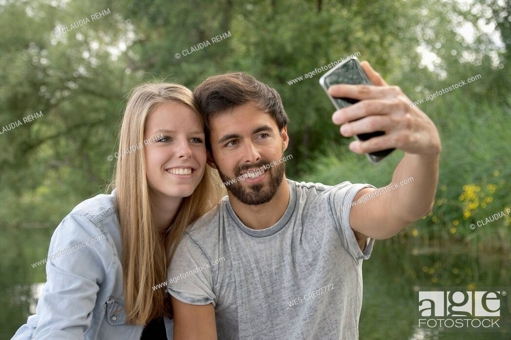 Imagen: Smiling young couple at a lake taking a selfie.