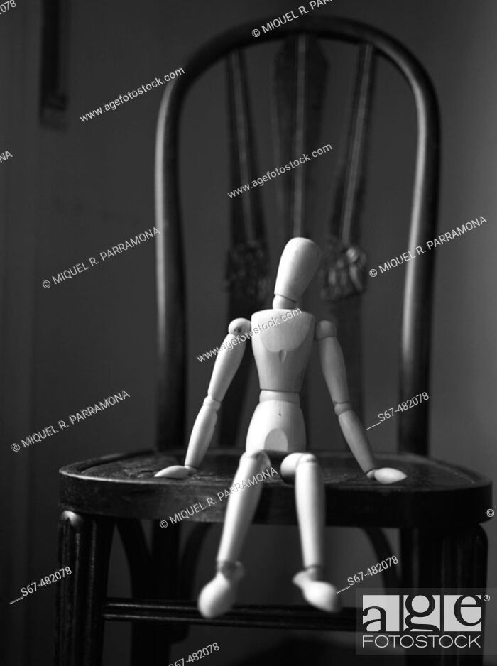Photo de stock: Wooden figure sitting on a chair in a fragility attitude.