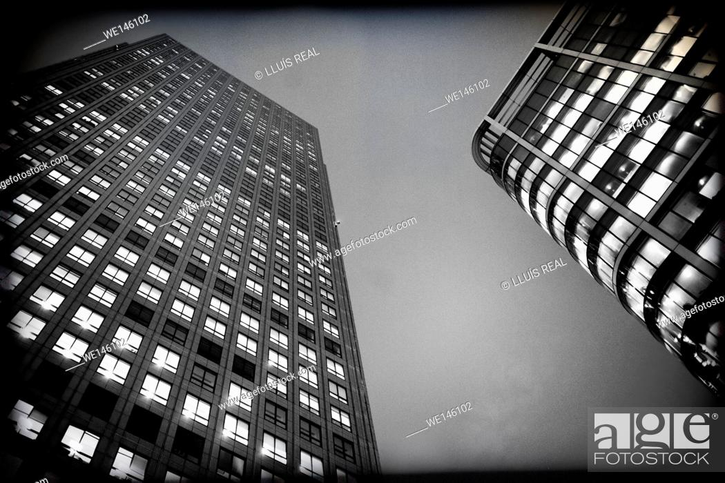 Stock Photo: Office building at night, with light in the windows in Canary Wharf, London, England, UK.