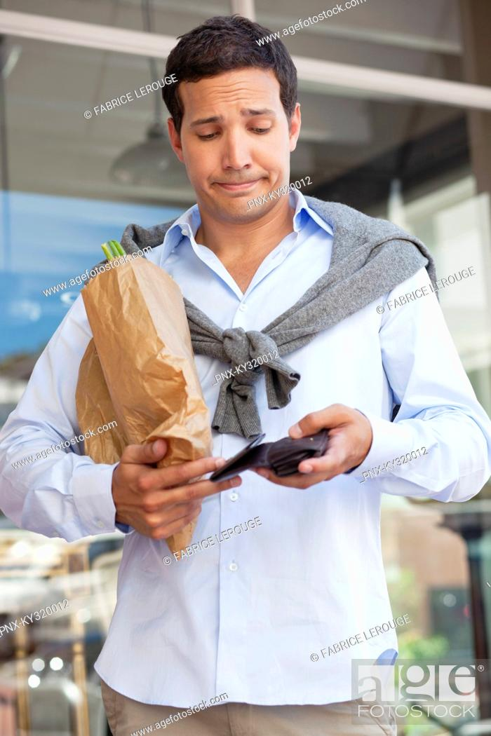 Stock Photo: Mid adult man checking the empty wallet with paper bag full of vegetables.