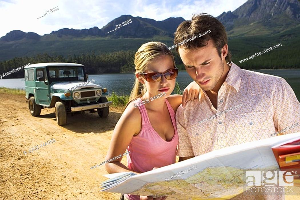 Stock Photo: Young couple standing near parked jeep on dirt track beside lake, consulting map.