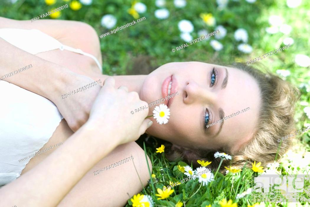 Stock Photo: Young woman lying on grass, holding flower, smiling at camera.
