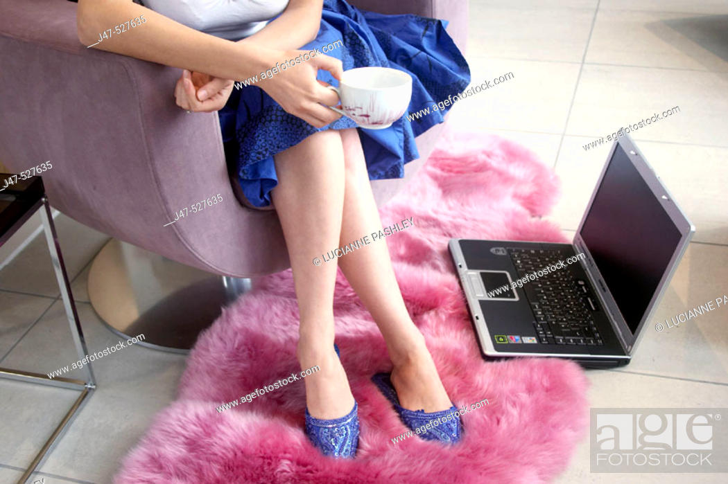 Stock Photo: legs and feet of young girl sitting with a laptop by her feet.
