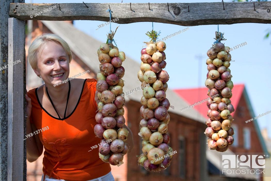 Stock Photo: Happy Smiling Young Woman and Onion Bundle, Kasepää Village, Tartu County, Estonia.