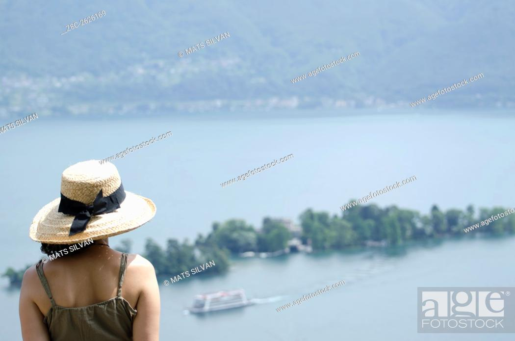 Stock Photo: Woman with a straw hat watching Brissago islands and passenger ship on alpine lake Maggiore in Ticino, Switzerland.