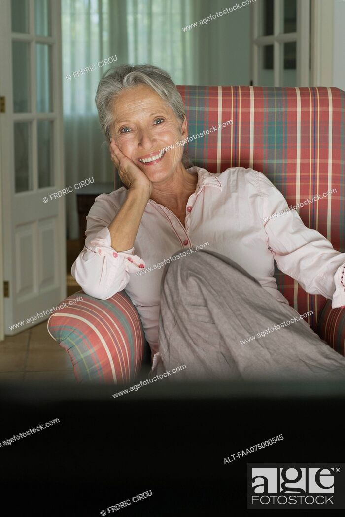 Stock Photo: Smiling senior woman sitting in armchair.