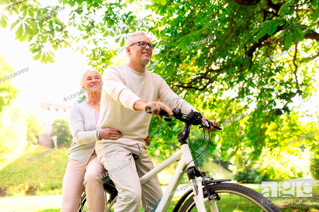 Stock Photo: old age, people and lifestyle concept - happy senior couple riding together on bicycle at summer city park.