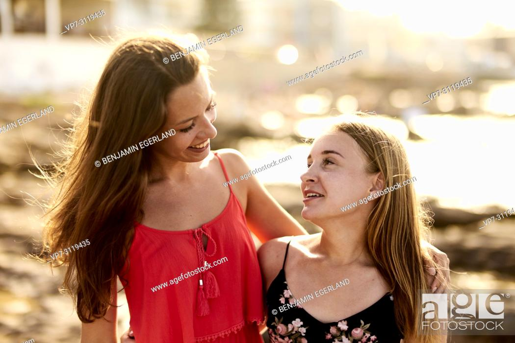 Photo de stock: two women, friends, at beach, togetherness in holiday destination Chersonisoss, Crete, Greece.