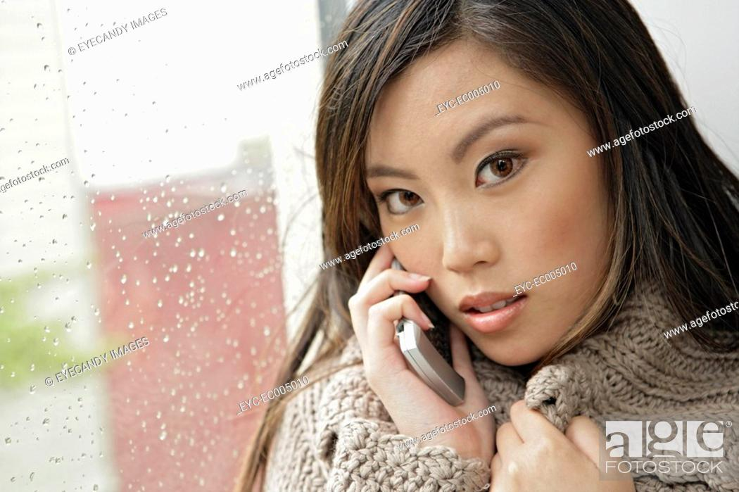 Stock Photo: One young woman using mobile phone, portrait.