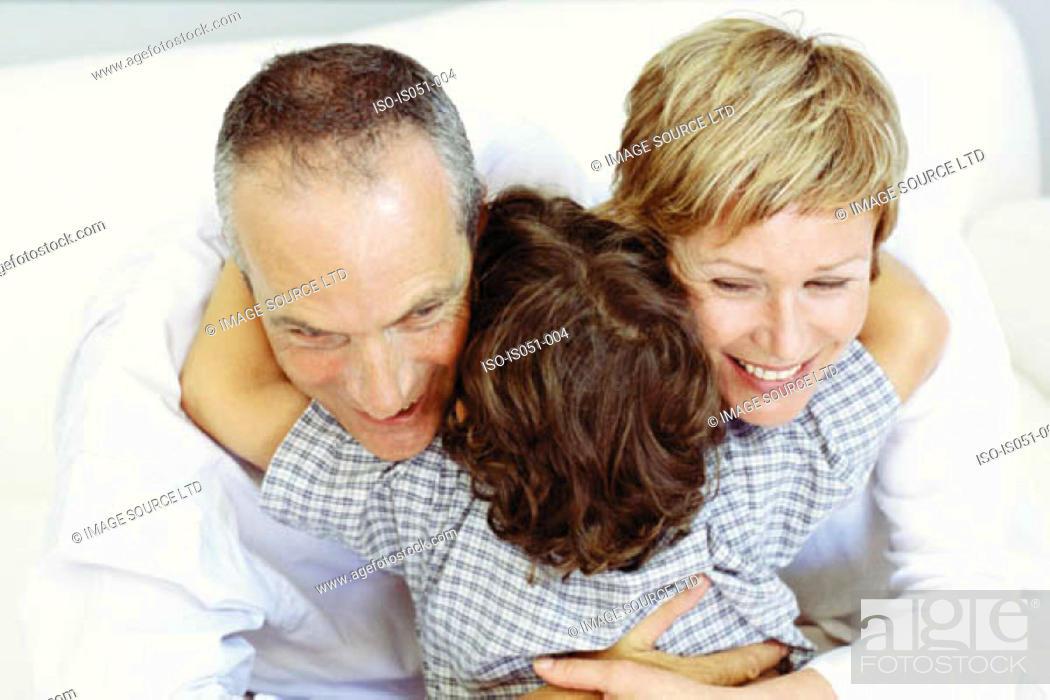 Stock Photo: Boy hugging grandparents.