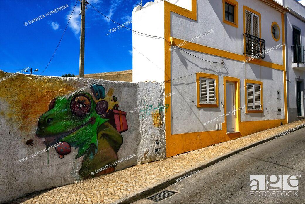 Stock Photo: Europe, Portugal, Algarve, Faro district, Lagos, old town, Rua da Atalaia, street scene with funny mural and unusually narrow house.