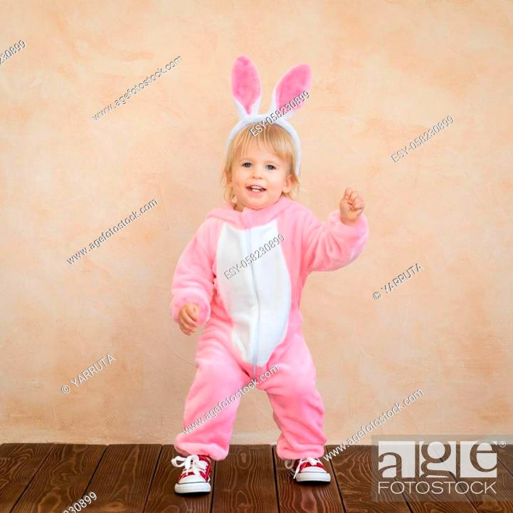 Photo de stock: Funny kid wearing Easter bunny. Child having fun at home. Spring holidays concept.