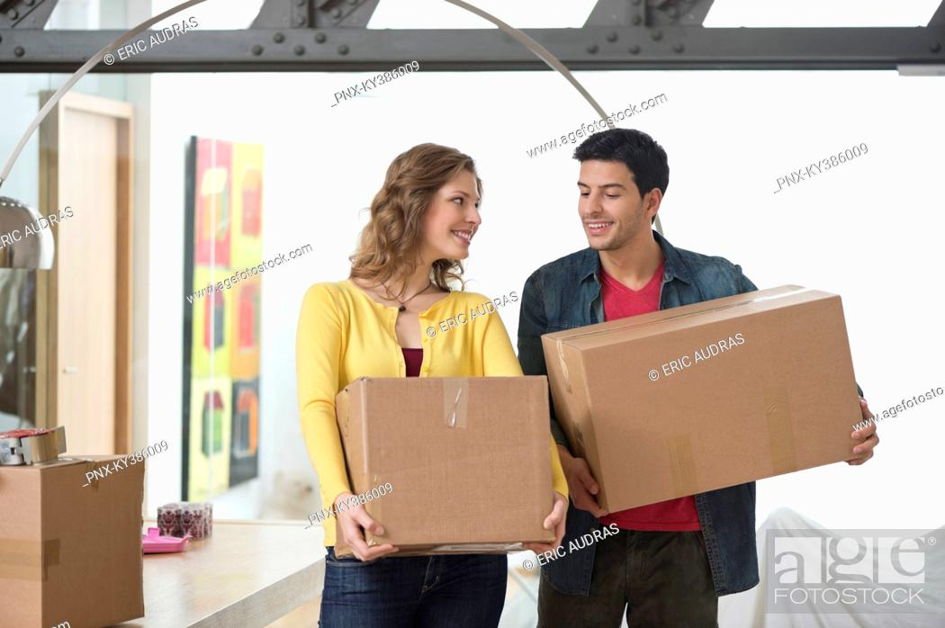 Stock Photo: Couple carrying cardboard boxes and smiling.