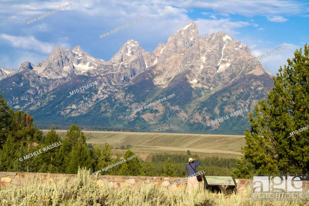 Stock Photo: Photographer taking a photo of the Grand Tetons.