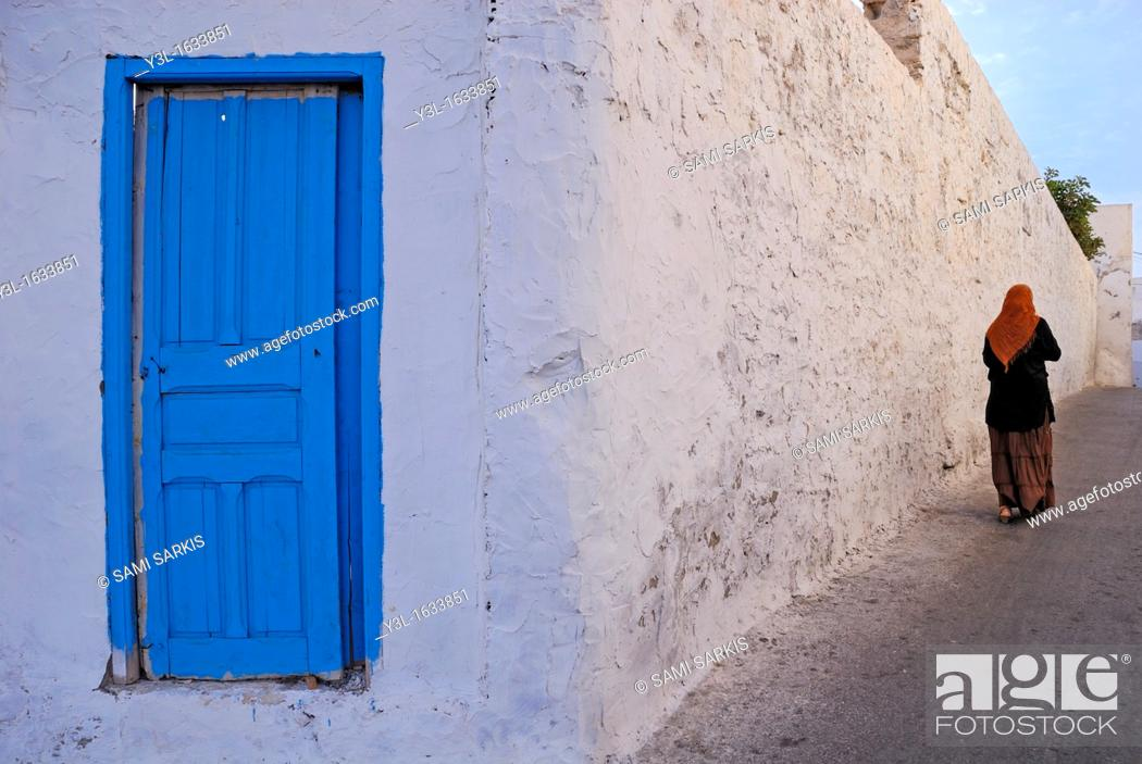Stock Photo: Woman walking by a white limed wall and blue door, Mahdia, Tunisia.