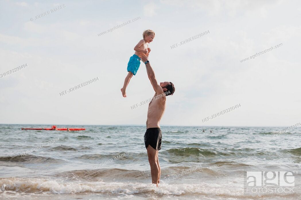 Imagen: Father playing with son on beach.
