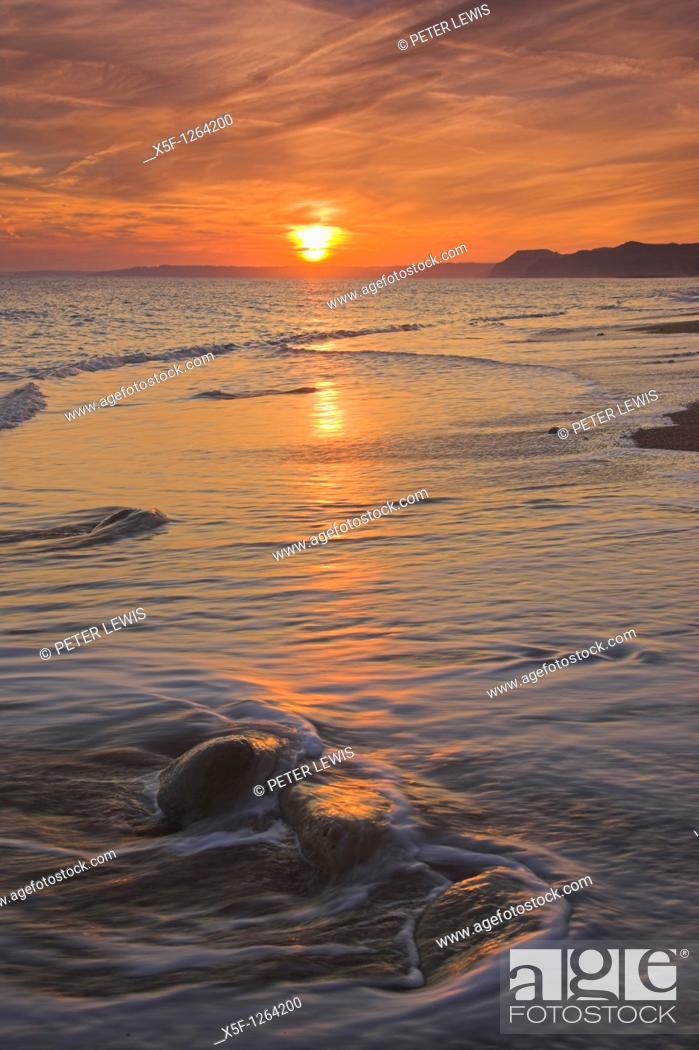 Stock Photo: Sunset on the beach at Burton Bradstock looking towards Lyme Regis in the Distance Dorset.