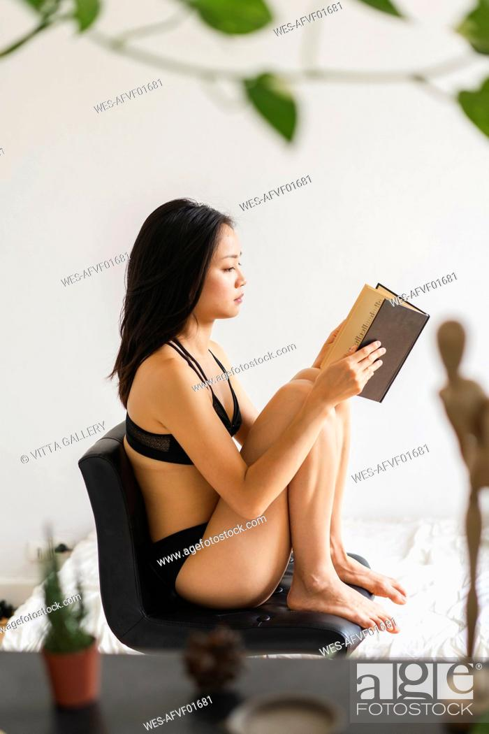 Stock Photo: Attractive young woman in lingerie sitting on chair at home reading book.