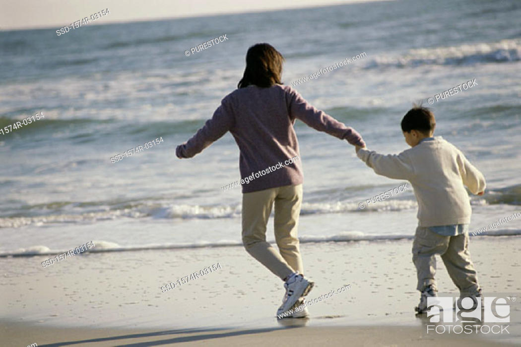 Stock Photo: Rear view of a mother and her son walking on the beach.