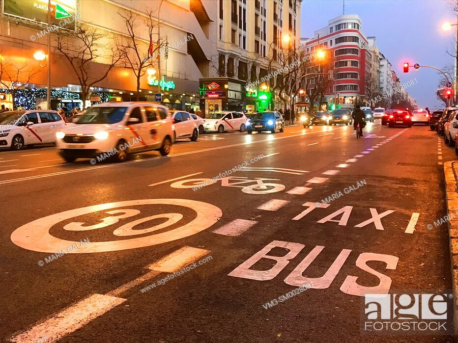Stock Photo: Bus-Taxi lane and cycle lane in Goya street, night view. Madrid, Spain.