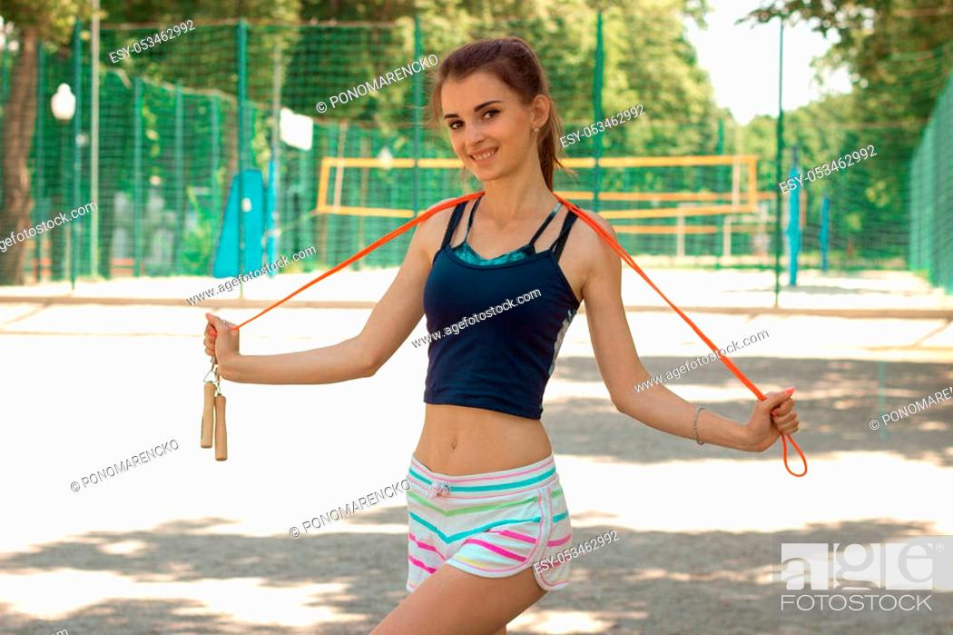 Stock Photo: beautiful skinny girl looks into the camera, smiling and holding a rope.