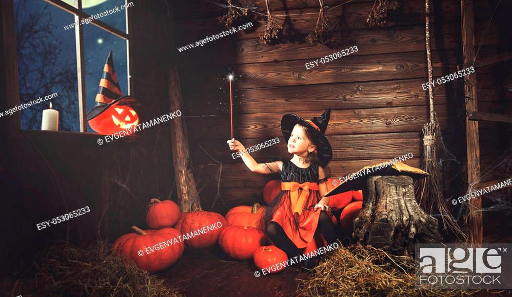 Stock Photo: Halloween. little witch child conjures with book of spells, magic wand and pumpkins.