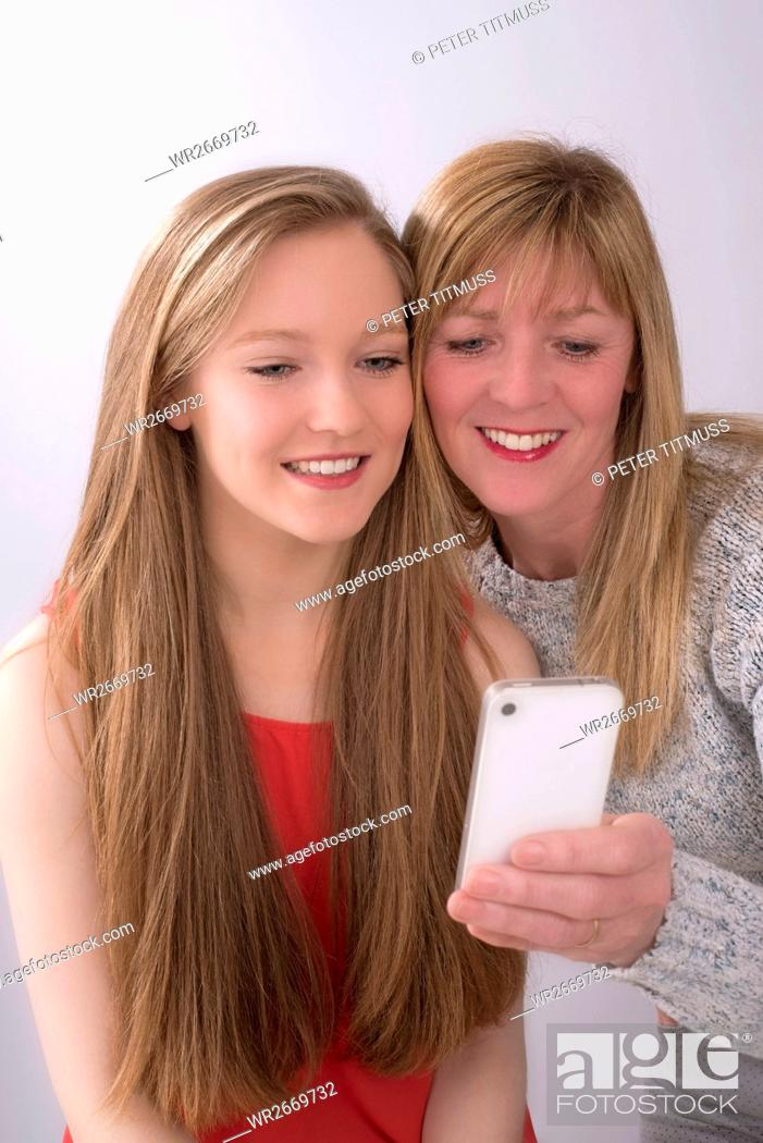 Stock Photo: Expressive portrait of mother and daughter using a mobile phone.