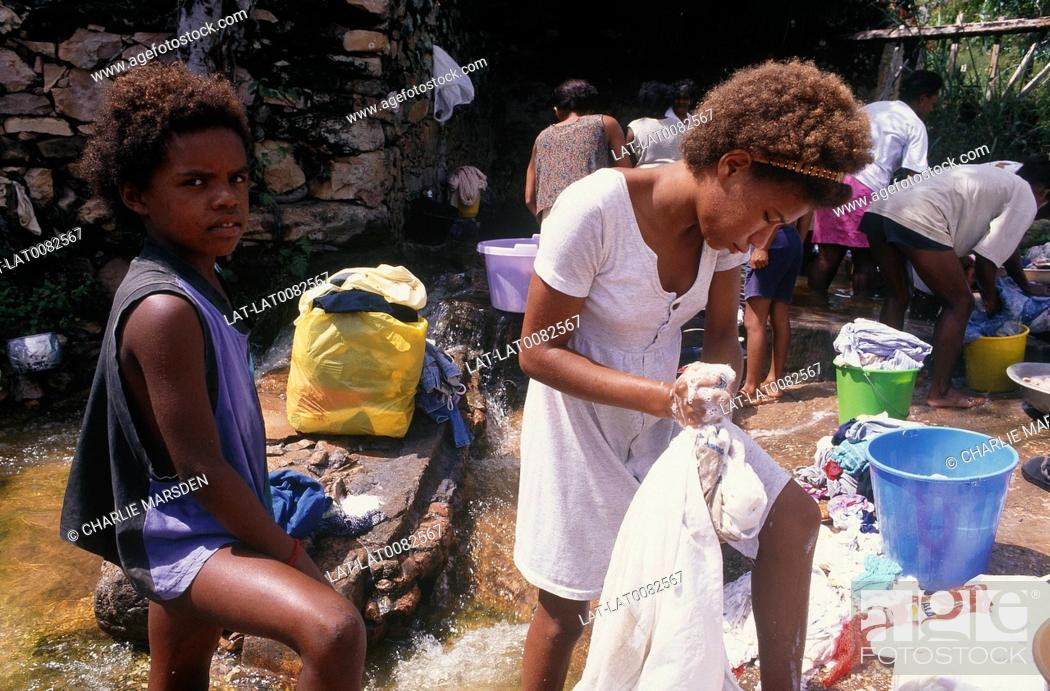 Stock Photo: Girl wringing cothes with soapy hands. Girl in black scowling. Women and girls washing clothes in stream.