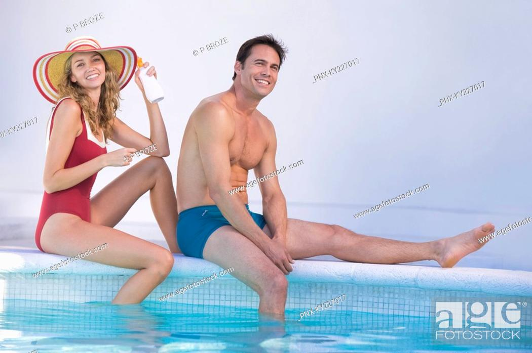 Stock Photo: Couple sitting at the poolside.
