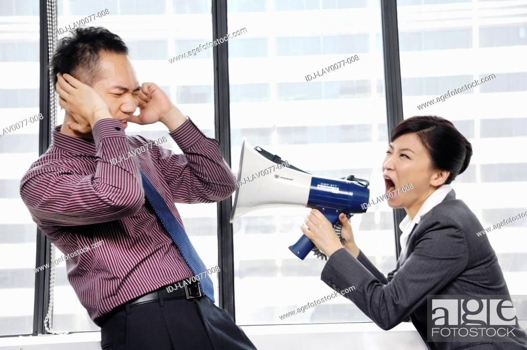 Stock Photo: Businesswoman yelling into a megaphone at her colleague.