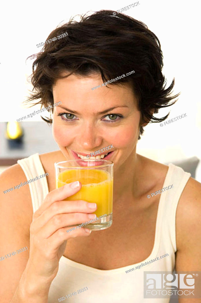 Stock Photo: Portrait of a young woman drinking orange juice.
