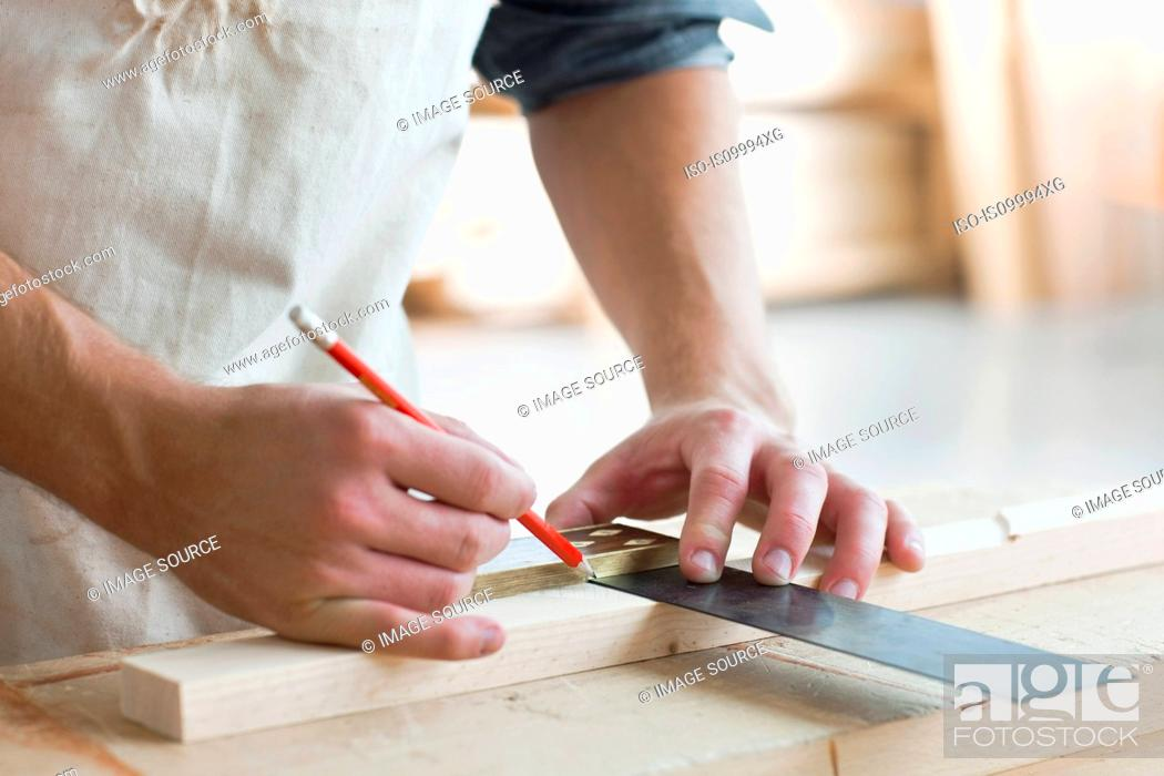 Stock Photo: Carpenter using mitre in workshop.
