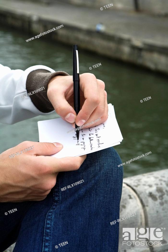 Stock Photo: Close up of young man writing postcard, Pont Neuf bridge, Paris, France.