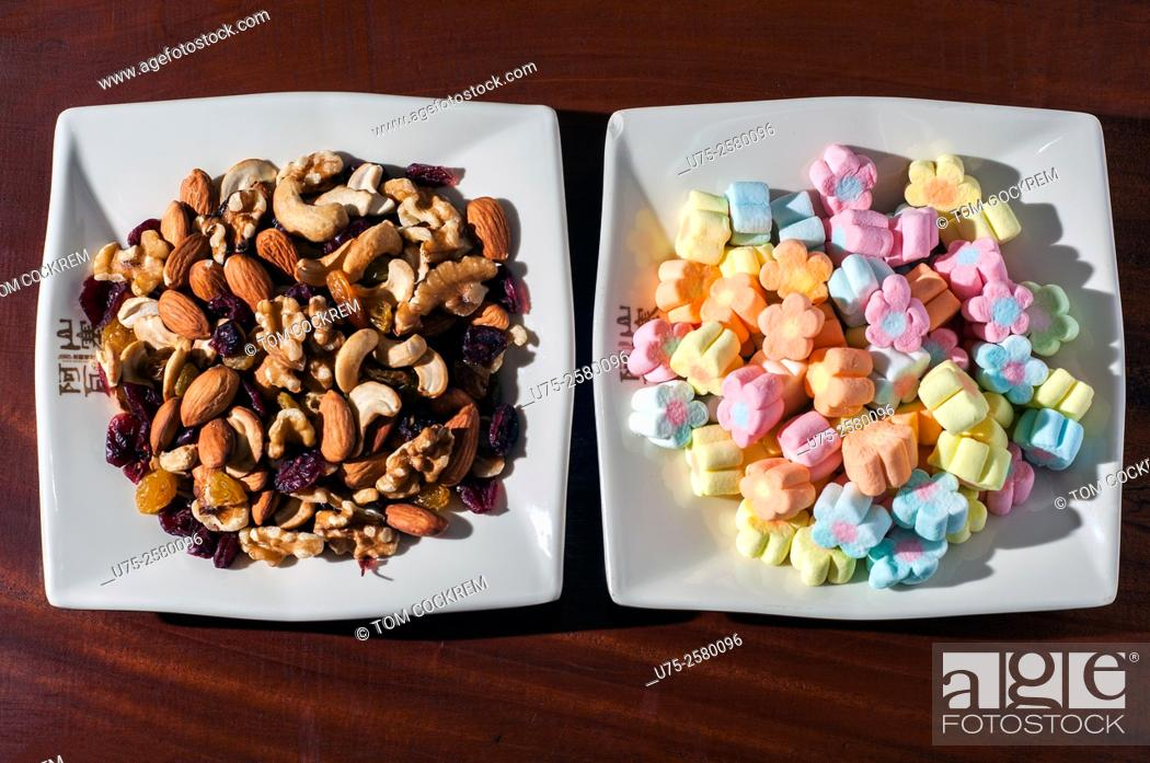 Stock Photo: Bowl of nuts and dried fruit alongside bowl of marshmallows in studio setting.