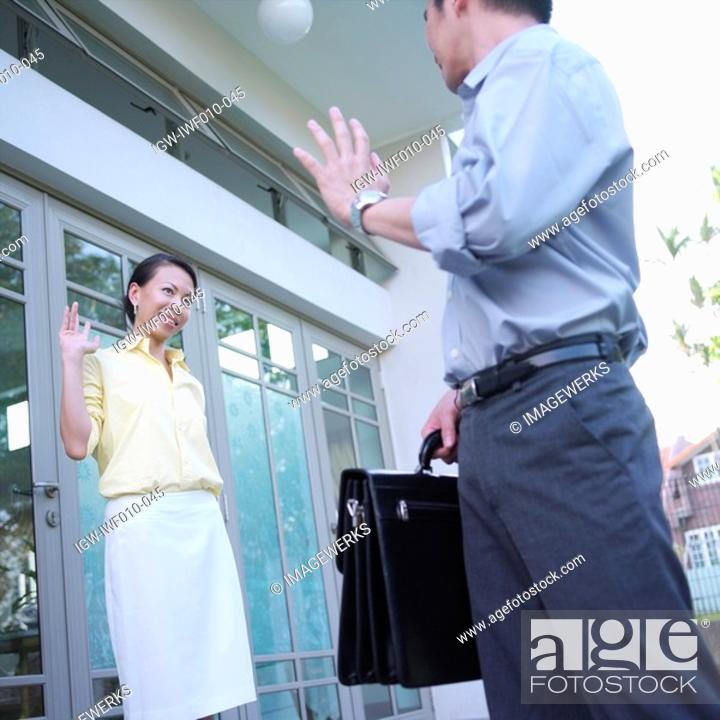 Stock Photo: Side profile of a mid adult man waving to a young woman.