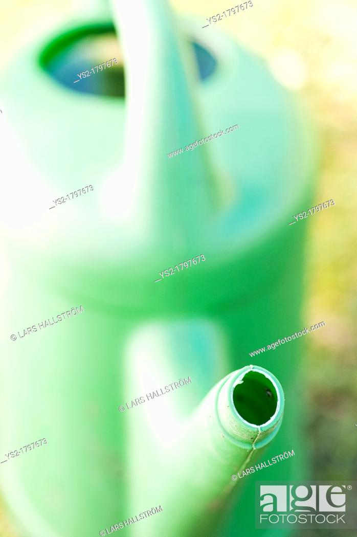 Stock Photo: Gardening equipment, green plastic watering can in a garden at summertime.