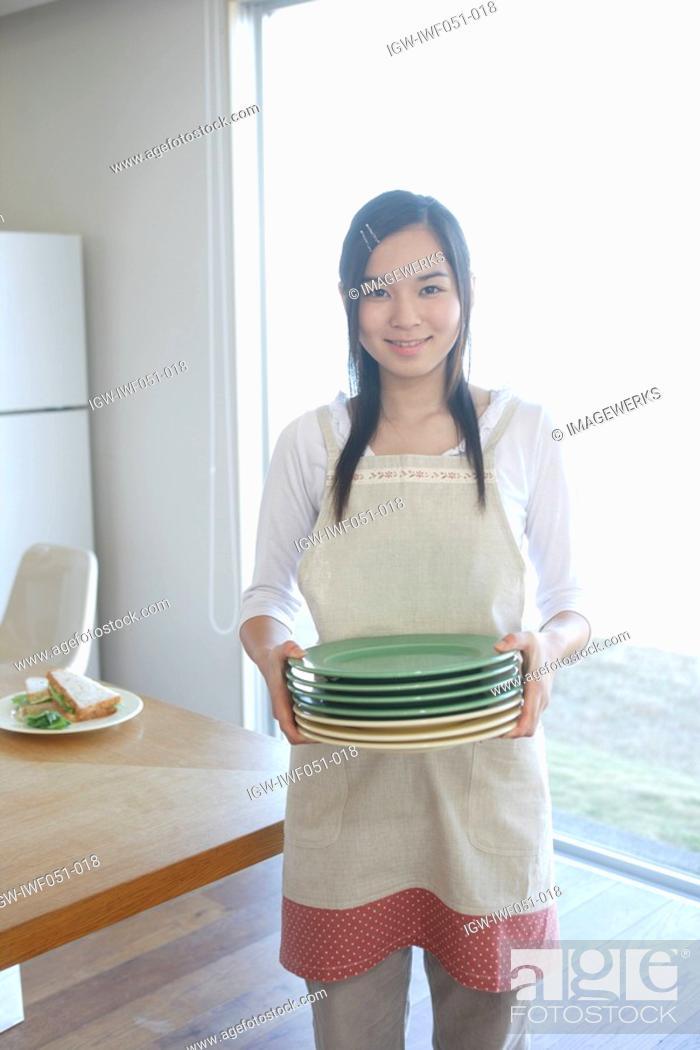Stock Photo: Teenage girl 14-15 holding stack of plates, portrait.