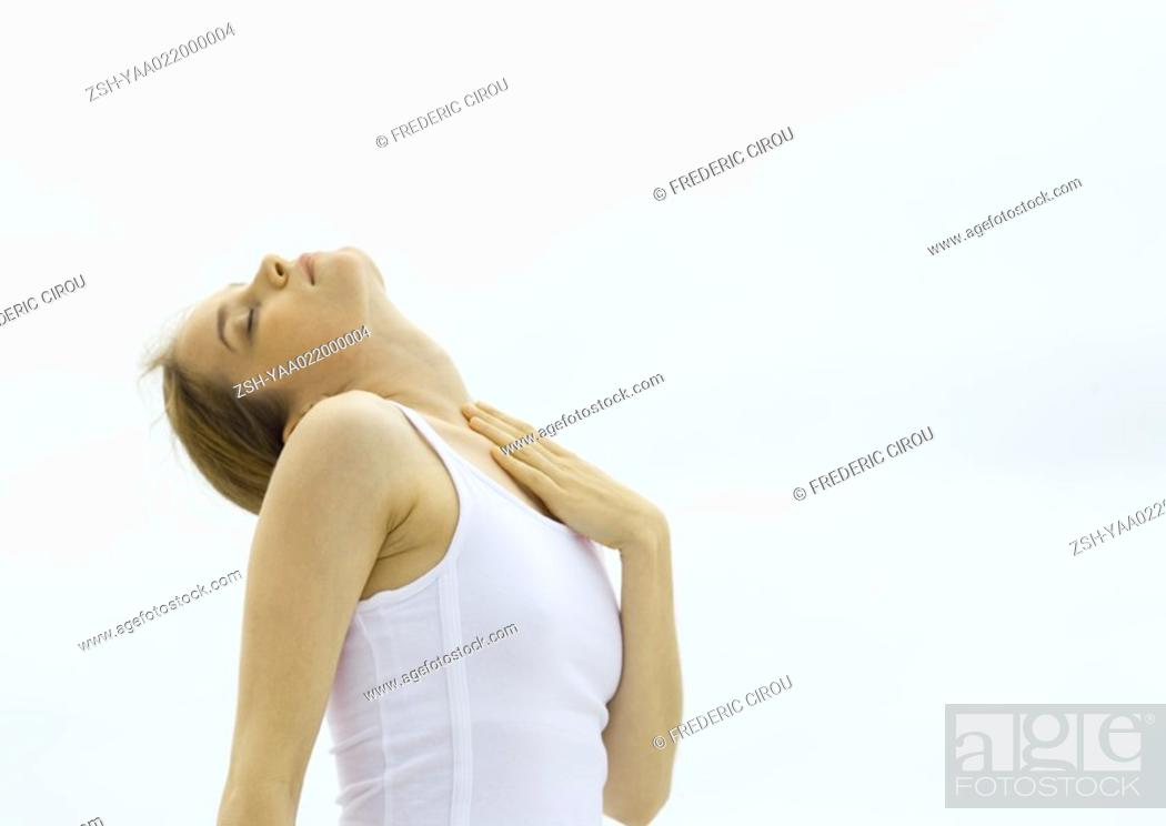 Stock Photo: Young woman with head back, touching chest.