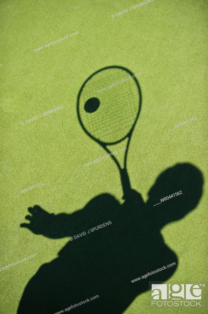 Stock Photo: The shadow of a tennis player cast on the court.